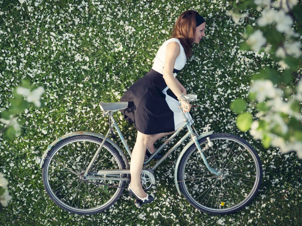 Overhead shot of woman in skirt on bicycle appears flat, a force perspective photography idea.