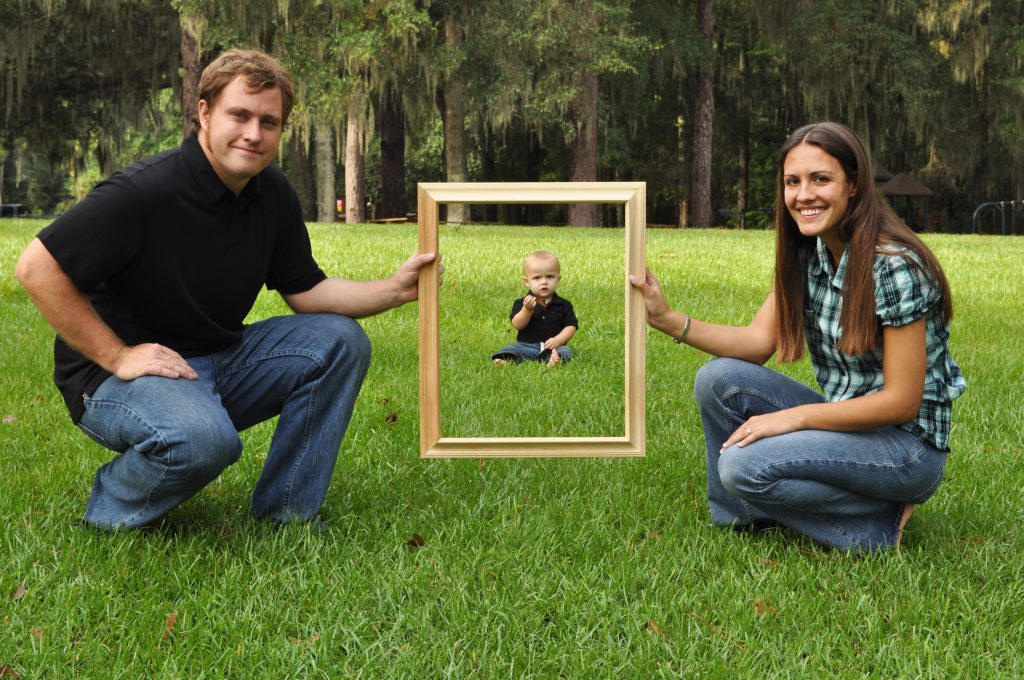 Mom and dad holding a picture frame with baby in background create forced perspective photography.