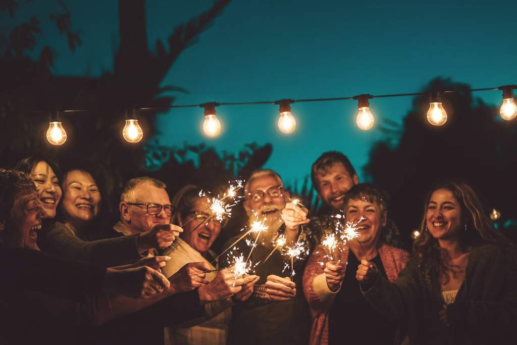 Happy family holds sparklers under string lights at night during backyard party.