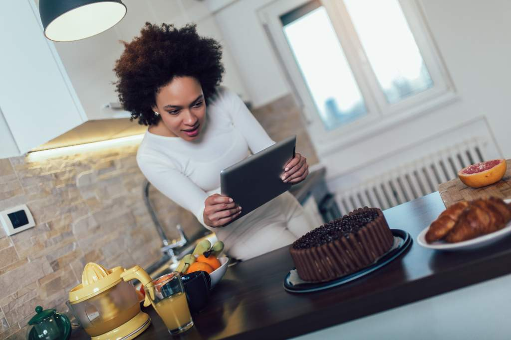 Woman uses iPad camera to take detailed photo of a chocolate cake on kitchen counter.
