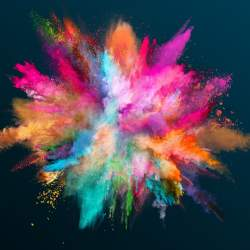 Various color powder explodes on black background to inspire better photo book design.