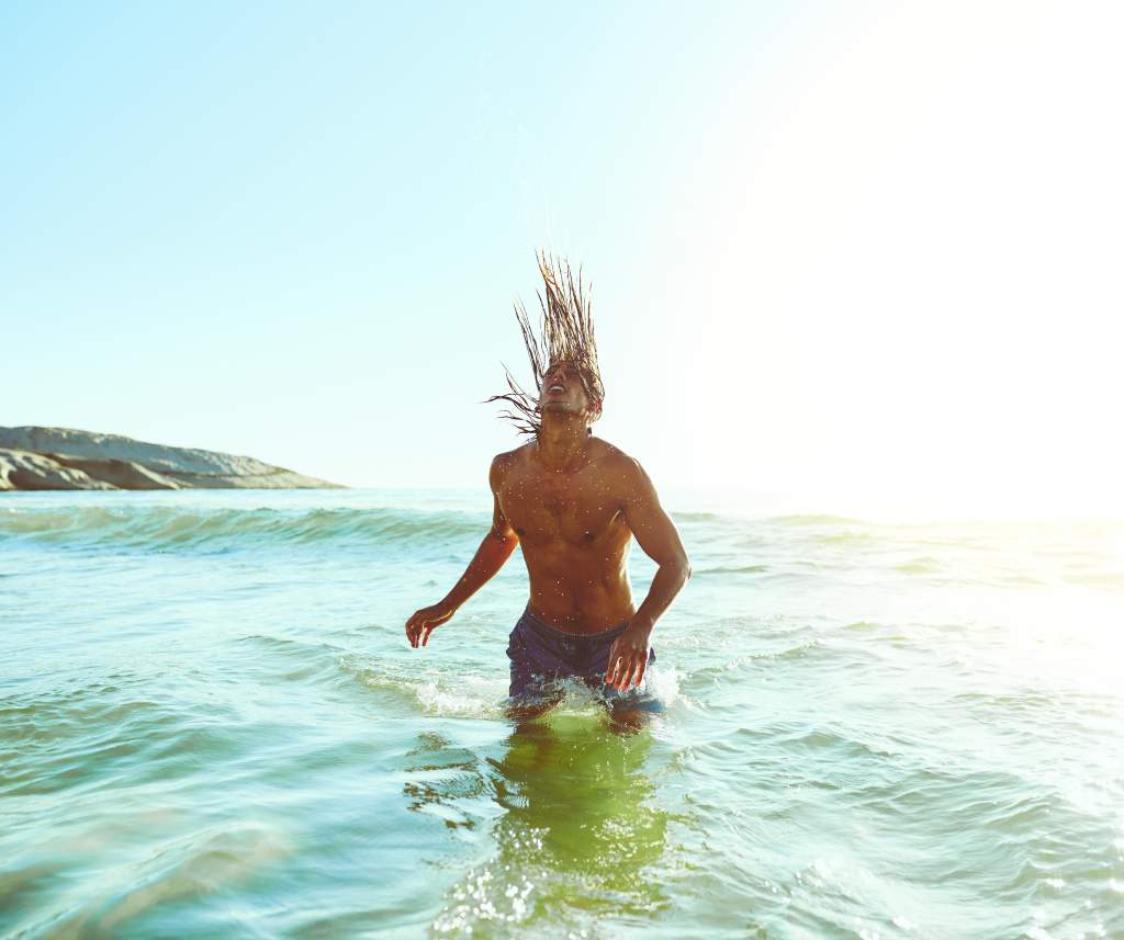 A man in the ocean demonstrates funny poses for pictures by flipping water with long hair.