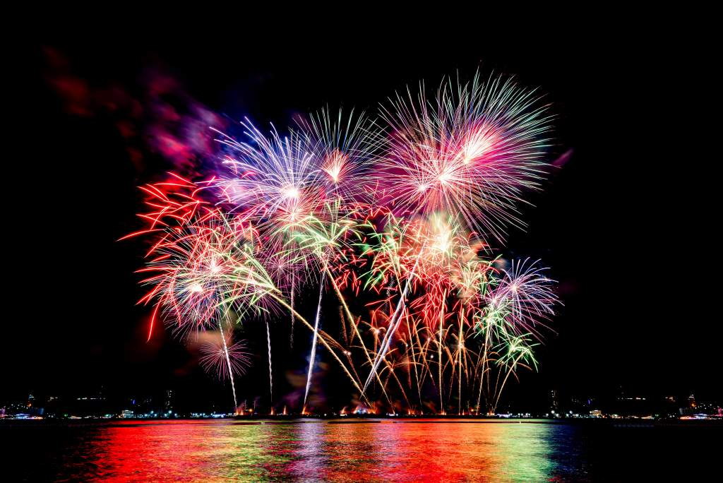 A colorful fireworks display over the beach reflects a rainbow in the water.
