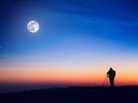 Photographer with tripod uses night photography tips to shoot the moon at sunset.