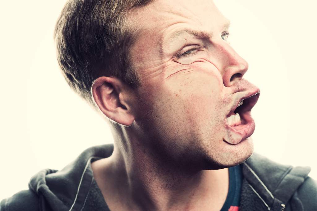 Man presses right cheek against clear glass to squish face and practice funny poses for pictures.