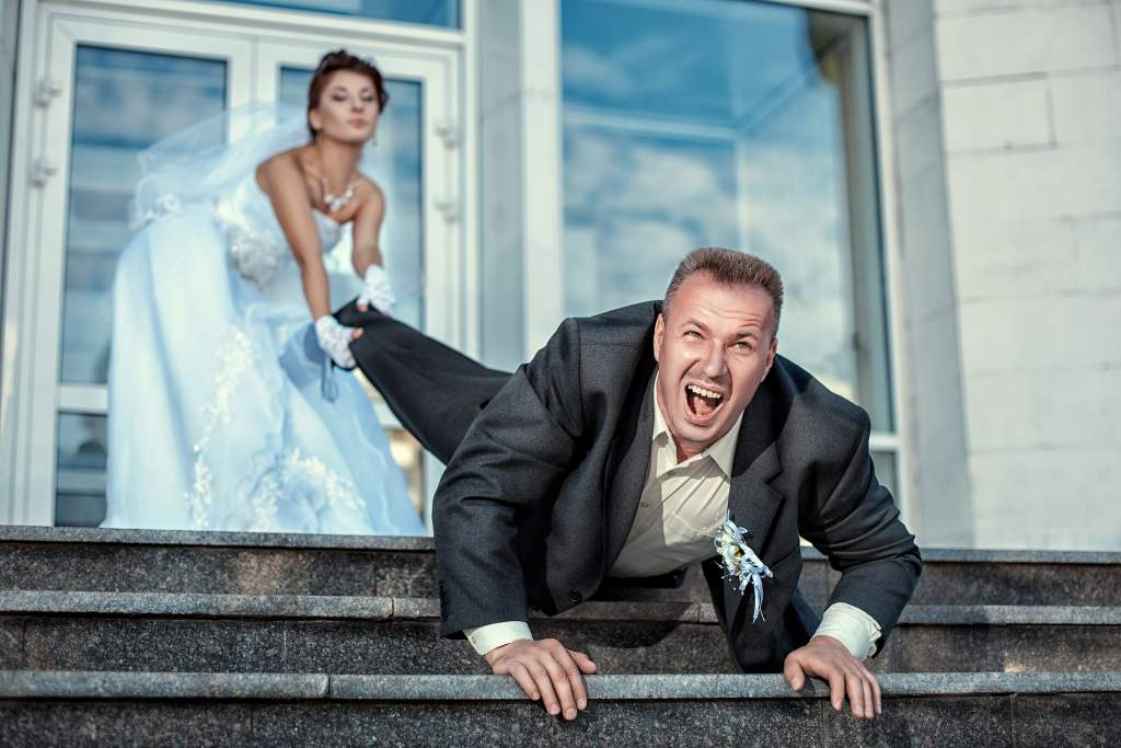 Funny poses for wedding pictures: bride pulls groom by the leg as he tries to crawl down stairs.
