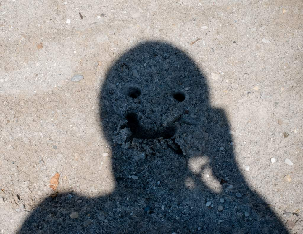 A person's shadow has eyes and mouth drawn in the sand to make a funny pose for pictures.