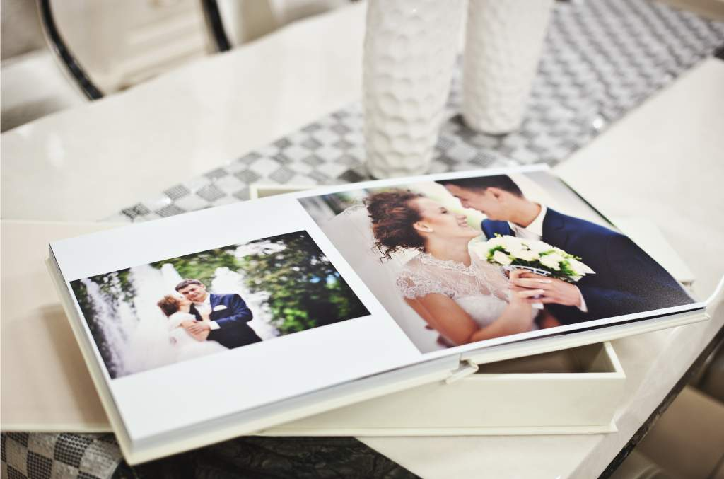 This open wedding album on a white table illustrates the most popular photo book idea.