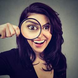 Dark-haired woman holds magnifying glass to eye, makes funny poses for pictures.