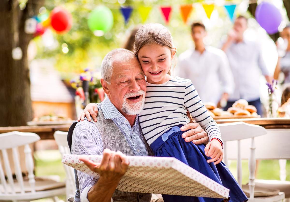 Grandpa and granddaughter celebrating a birthday outside is the perfect photo book idea.