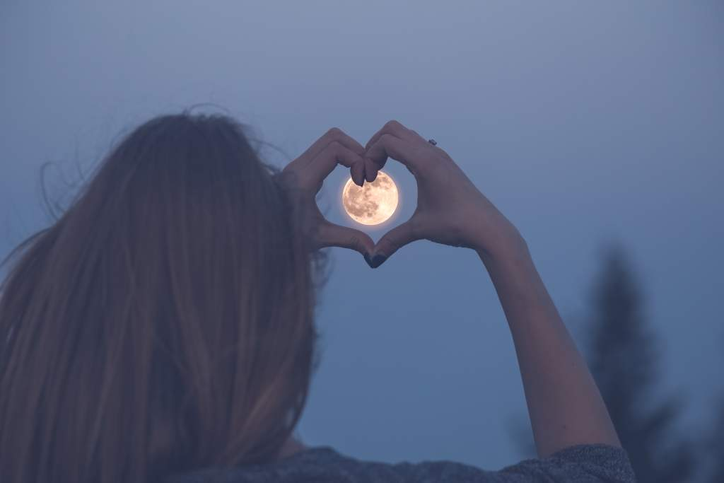 Woman uses hands to form a heart around the full moon in clear blue night sky.