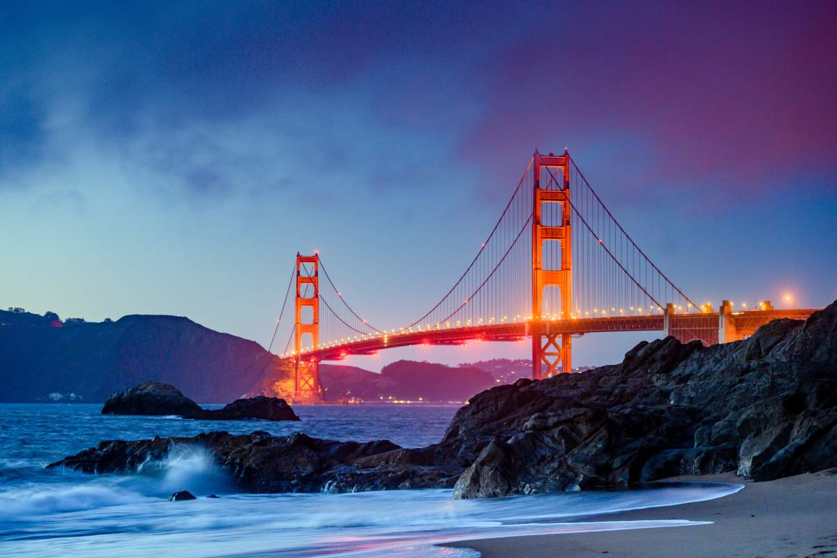 A photo of Golden Gate Bridge at dusk in low lighting can be taken with iPhone Night mode.