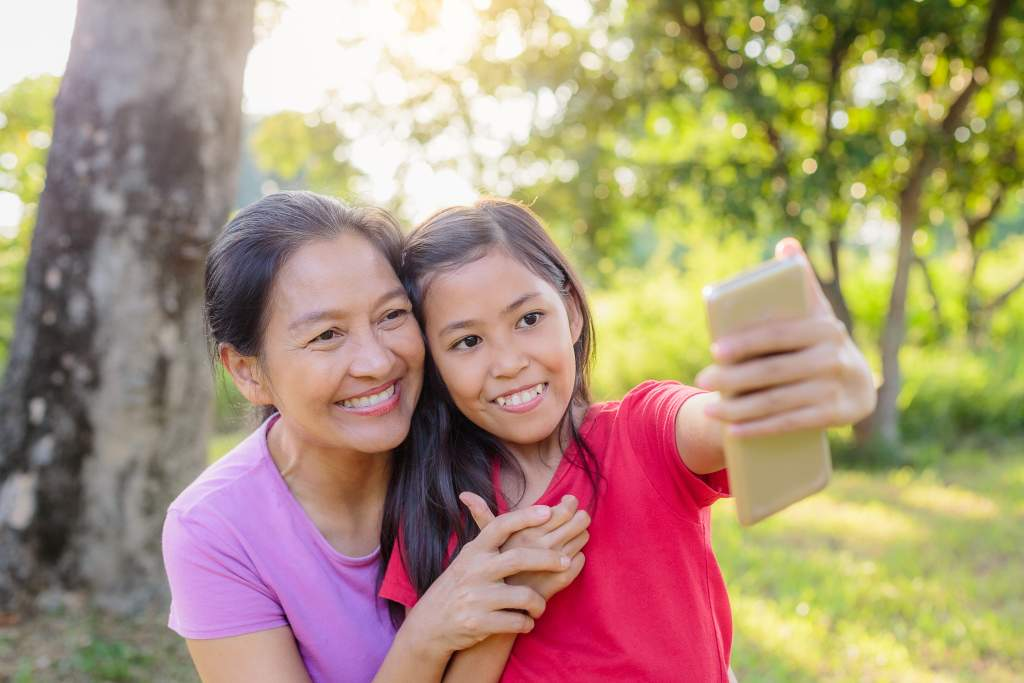 Young girl uses the iPhone 11 camera lenses to take selfie with her grandmother.