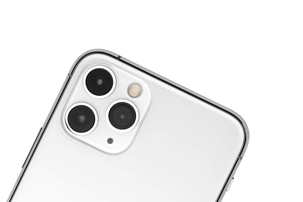 A close-up of a white iPhone 11 and its iPhone camera lenses on white background.
