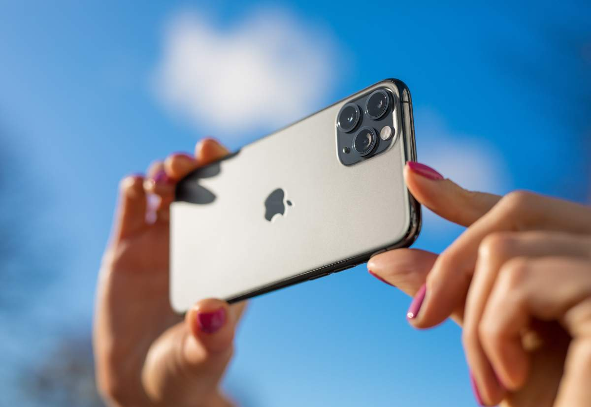 Woman's hands hold up iPhone 11 to the sky to test the 3 iPhone camera lenses.