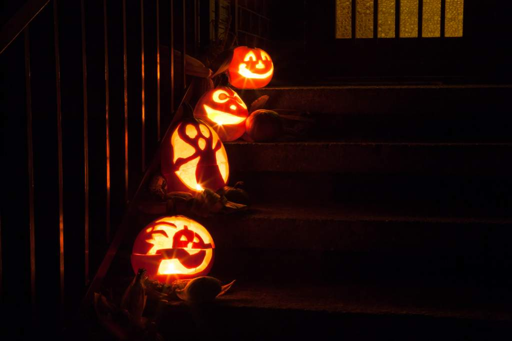 An outdoor staircase with four jack-o-lanterns lit up at night make cute Halloween photos.