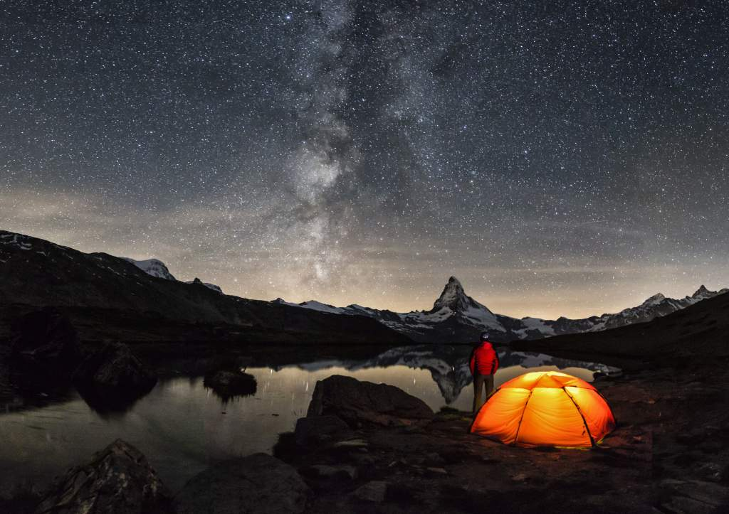 A photo of person in red next to well-lit tent under Milky Way is taken with iPhone Night mode.