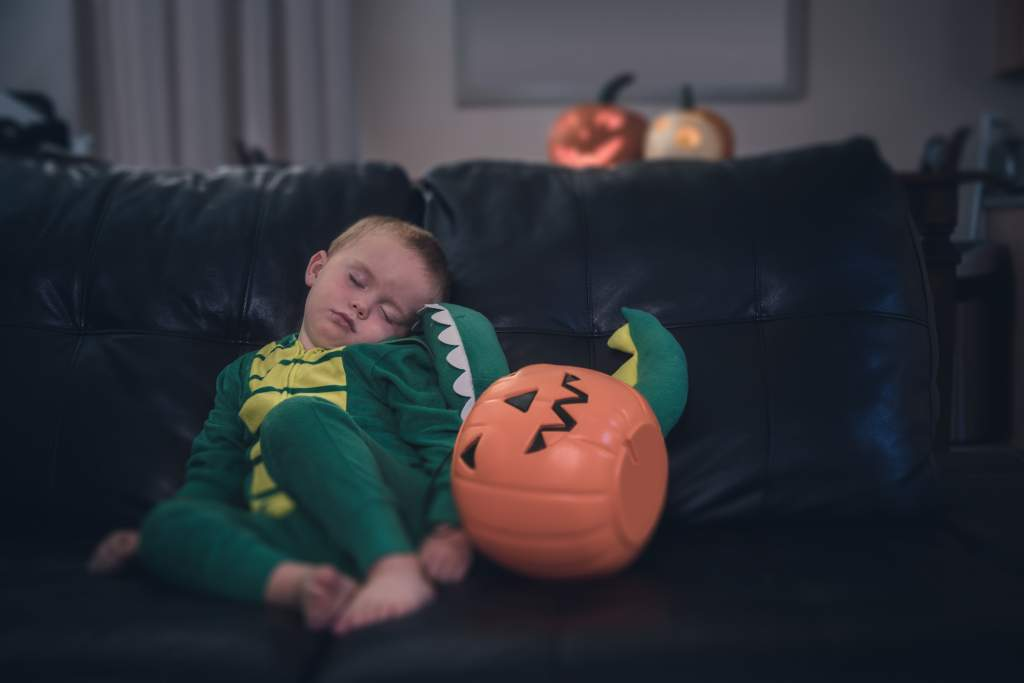 Little boy asleep on couch in dragon costume is the perfect setting for cute Halloween photos.