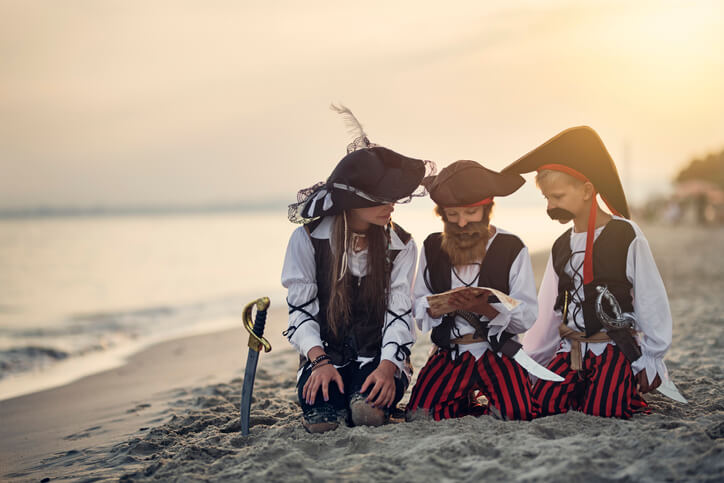 3 kids dressed as pirates read treasure map on the beach for Halloween photoshoot.