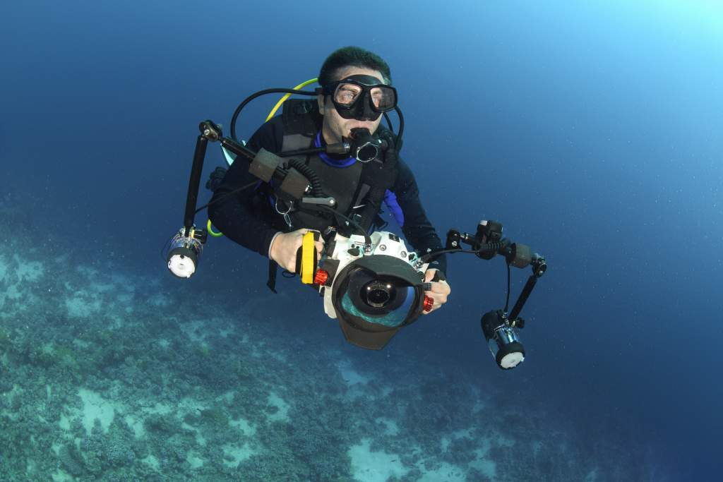 Male scuba diver shooting underwater photography with camera housing, strobes, and lights.