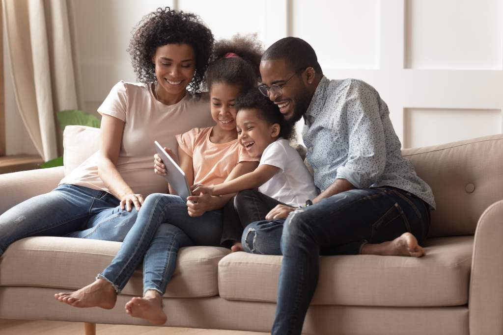 An African American family gathers on couch with iPad, smiling about their Apple photo book.