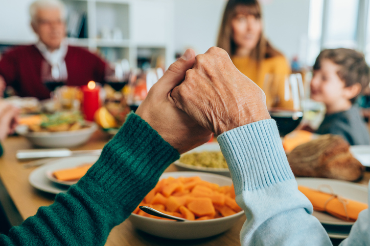 Closeup of two people holding hands for the blessing is a great Thanksgiving photo card idea.