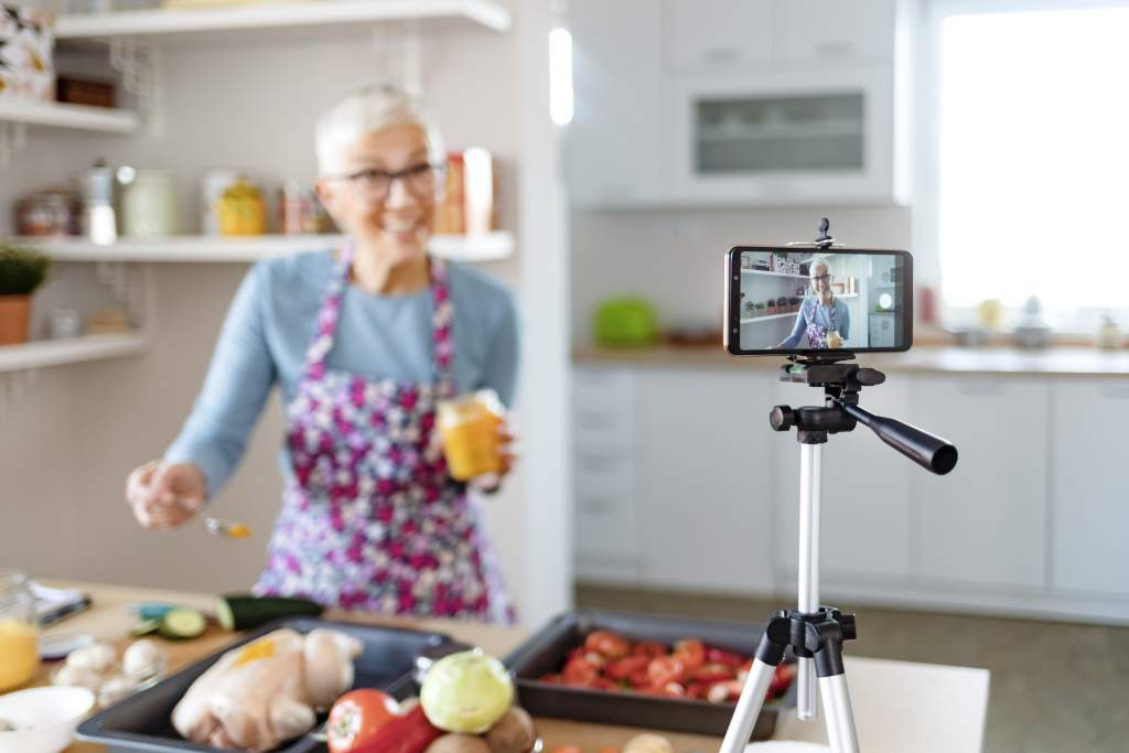Senior woman films cooking demo in kitchen with an iPhone vs. DSLR because of image quality.