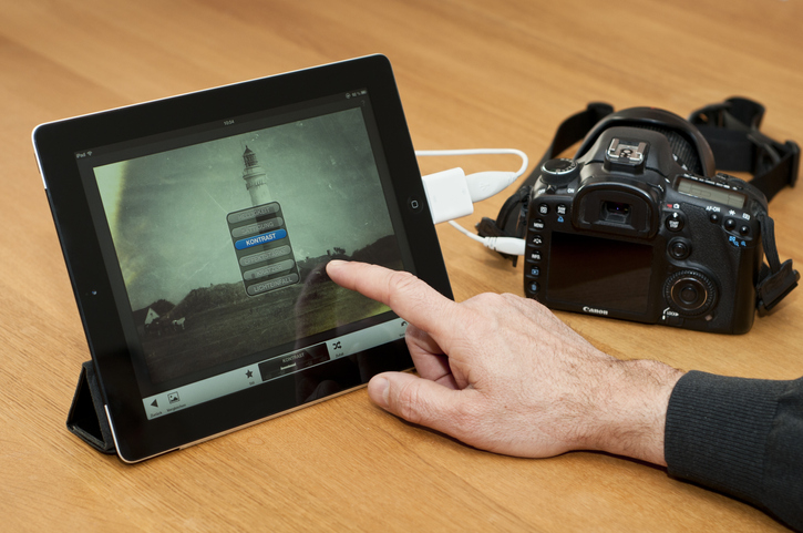 Man's hands show how to connect DSLR to the iPad using adapter cords.