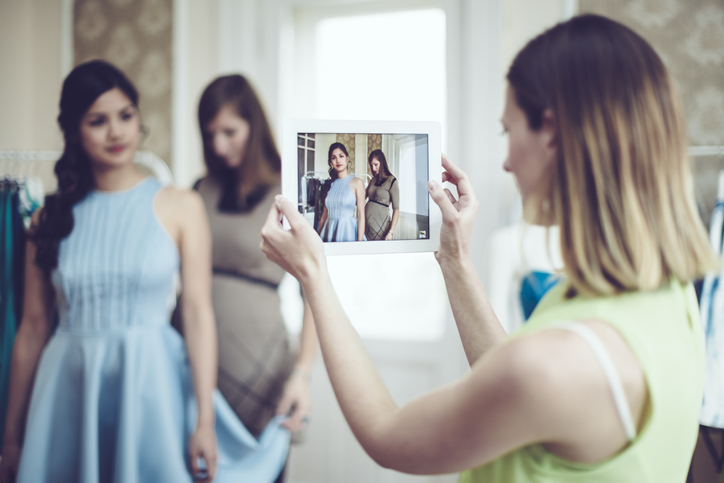 Young woman takes photography on iPad to capture young girl getting fitted for blue dress.