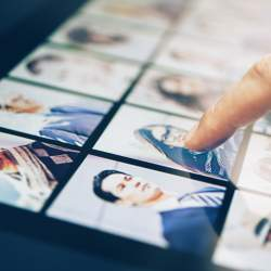 A man's finger scrolls through headshots, ready to find out how to convert iPad photos to JPEG.