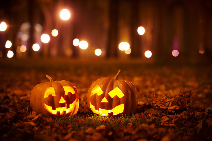 The best Halloween photoshoot ideas might include 2 jack-o-lanterns lit up at night in the woods.