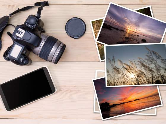 A smartphone, a camera and printed photos on wood background illustrate iPhone vs. DSLR debate.