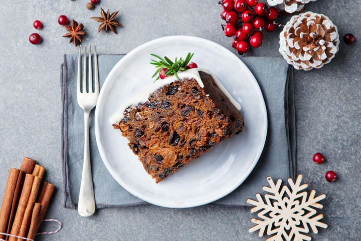 Christmas photography can be a slice of fruit cake on white plate with fork and seasonal décor.