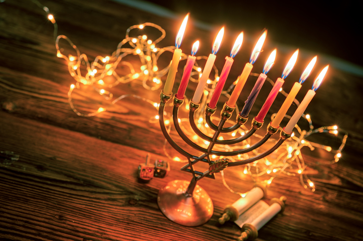 Focusing on the menorah lights in the dark is a traditional Hanukkah greeting card image.