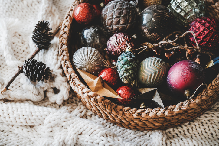 Christmas photography should include a collection of ornaments in wicker basket on knitted blanket.