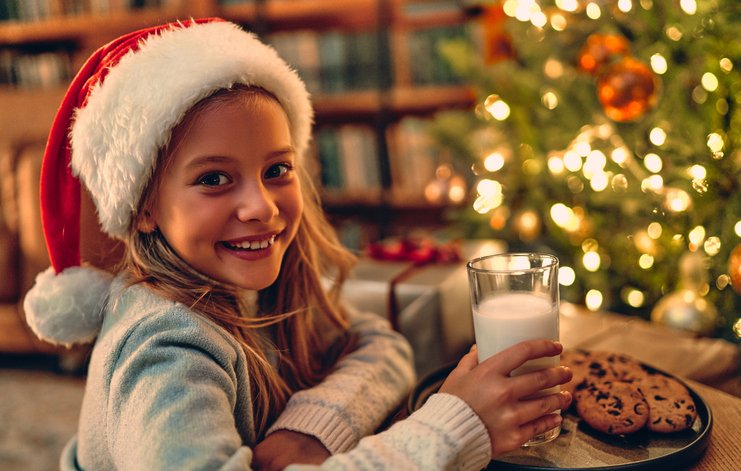Young girl enjoys milk and cookies for Santa in front of the Christmas tree.