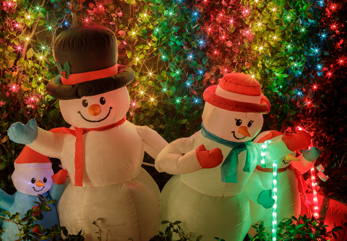 Focus on inflatable snowmen in front yard to make your custom Christmas card.