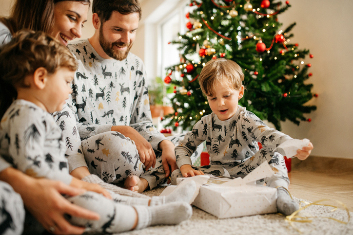 Photo of mom, dad and 2 kids in matching PJs opening presents is cute Christmas card idea.