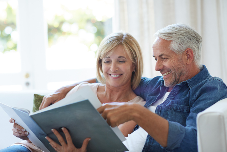 A middle-aged couple sits on couch, flipping through a DIY custom photo book.