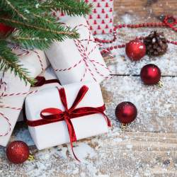DIY Christmas gift ideas wrapped in white paper and red ribbon sitting under tree on hardwood.