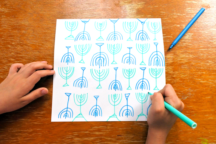 A child draws menorah shapes in blue and teal to create a homemade Hanukkah greeting card.