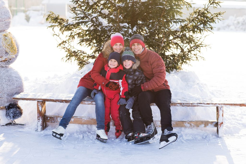 Beautiful family walking and playing on the ice in winter.