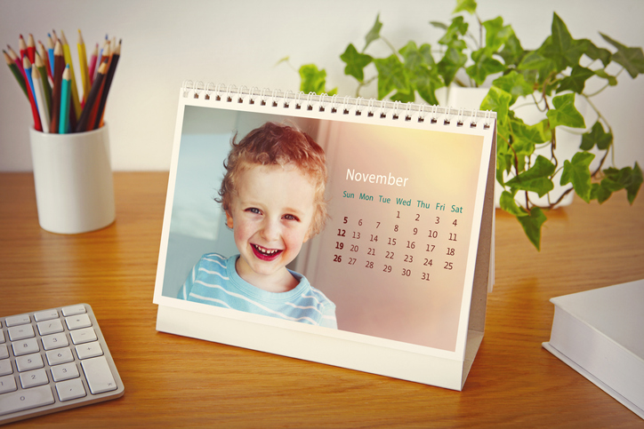 A small custom calendar with photo of little boy sits on wood desk with pencils and keyboard.
