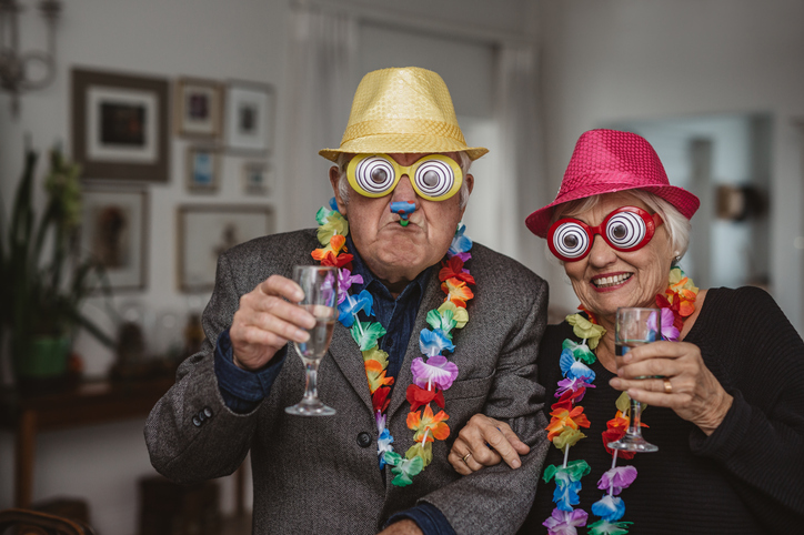 Senior couple wearing funny glasses and Hawaiian leis makes funny New Year's Eve pictures.