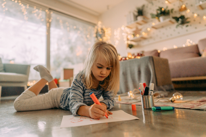 Little girl draws a picture by hand to make DIY Christmas cards this year.