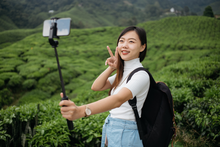 Asian woman holds selfie stick on tea plantation, one of the best photography gifts for level.