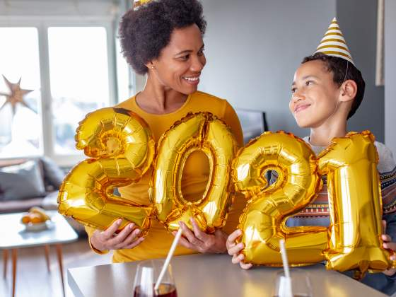 Mom & young son wear festive hats and hold '2021' balloons at home to take New Year's Eve pictures.