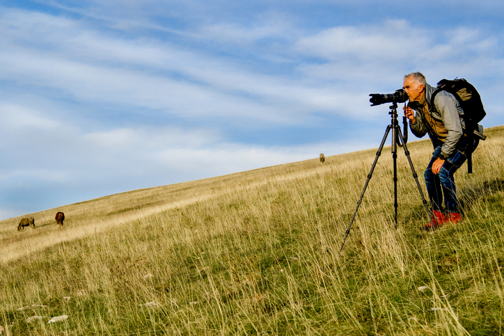 Man uses tripod and telephoto lens in a field, two of the best photography gifts.