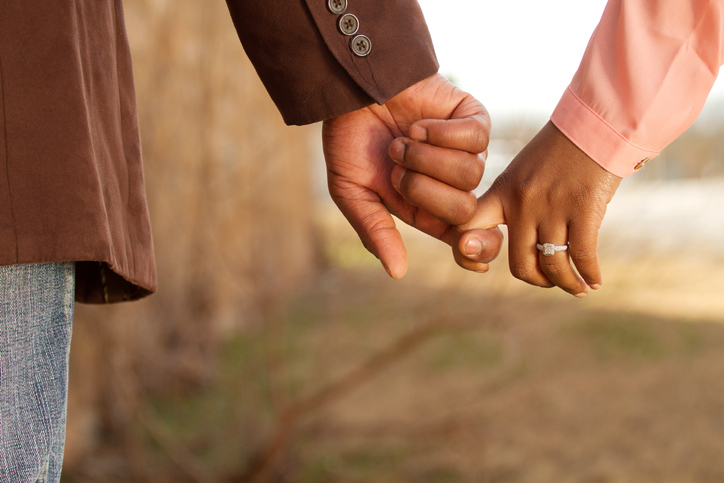 Closeup of African American male and female hands show off new ring in engagement photos.