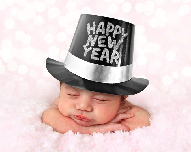 Baby New Year picture features newborn girl sleeping on pink blanket with festive black hat.